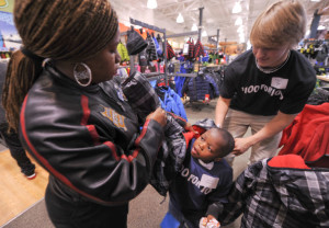 Jaquan Williams tries on a coat with help from his mother, Crystal Moyd, and John Tyson, a junior at St. Christopher's School, during the RVA $100 for 100 shopping trip to Dick's Sporting Goods at Short Pump Town Center. Photo: Clement Britt.